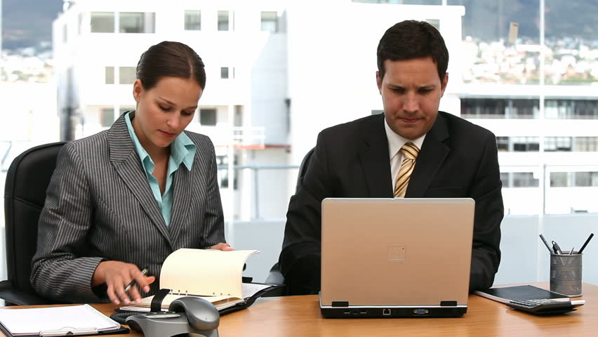 Two serious businesspeople working together in an office - HD stock footage clip