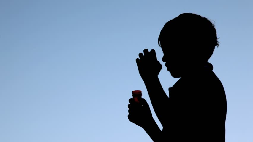 silhouette of boy blowing up soap bubbles against blue sky