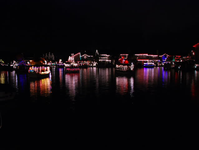 Boat parade on a lake with Christmas lights reflecting on the water.  - SD stock footage clip