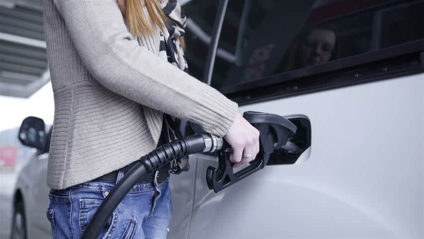 Almost finished fueling up gasoline in car 4K. Female person fueling up car, holding gasoline handle to fill up empty tank. Close up.