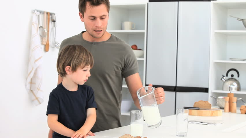 A dad serving a glass of milk to his son - HD stock footage clip