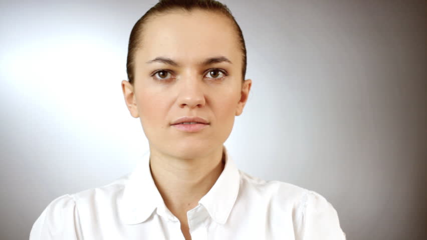 Portrait of a surprised young woman, gray background - HD stock video clip