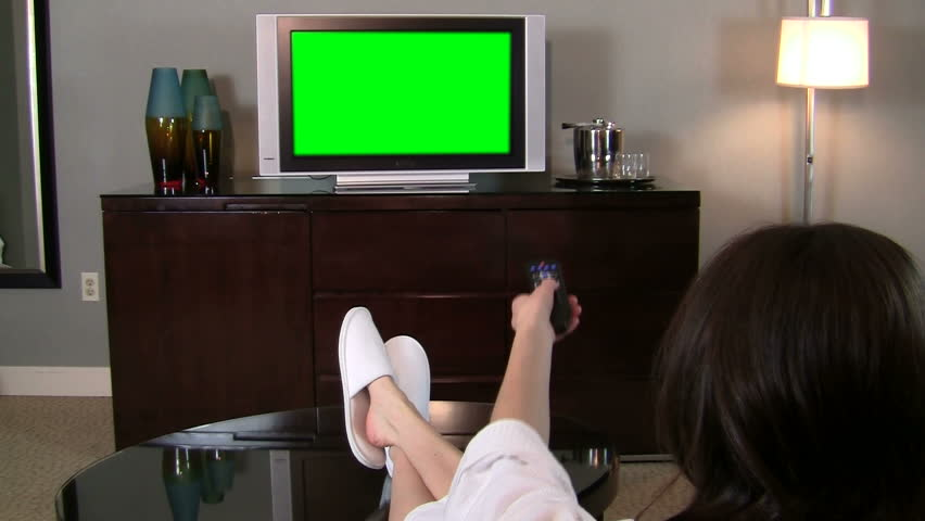 Woman flips channels on green screened TV with remote - HD - HD stock video clip