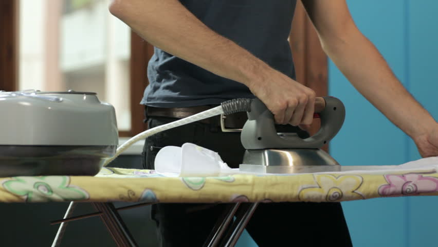 panning on caucasian adult man ironing white shirt at home - HD stock video clip