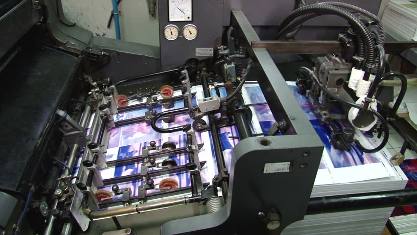 Pages being fed into a two color offset printing press. All the photographic images in this clip are property released. - HD stock video clip