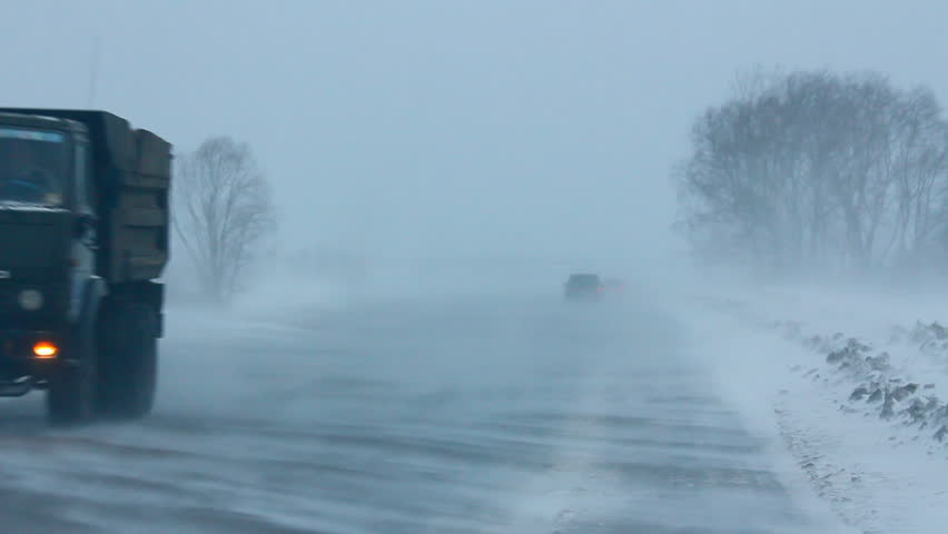 cars on winter road during blizzard - HD stock video clip