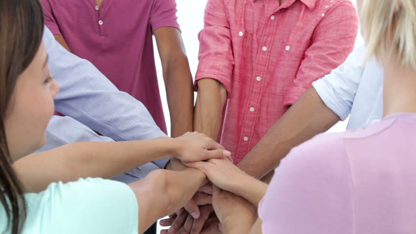 Close up of a group of young people joining hands in celebration.Shot on Canon 5D MkII at 25fps