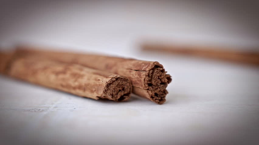 Cinnamon sticks HD stock footage. Close up dolly shot of some Cinnamon sticks against a white rustic background.