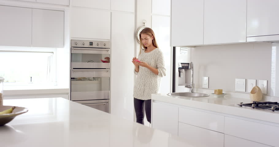 Woman in smart connected home using phone online internet of everything to enjoy a digital lifestyle