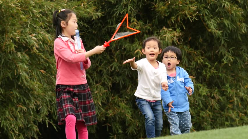 Shanghai,CHINA-May,2015 :Chinese children playing soap bubble in central park on May 16,2015 - 4K stock footage clip