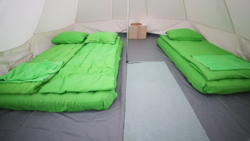 Interior of white tent with sleeping bags for tourists