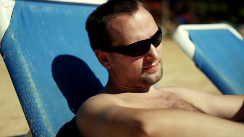 Man on the beach applying protection lotion - HD stock footage clip