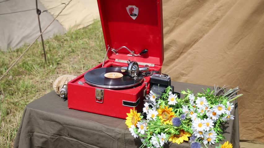 Gramophone, plate camera, canteen and flowers on the table