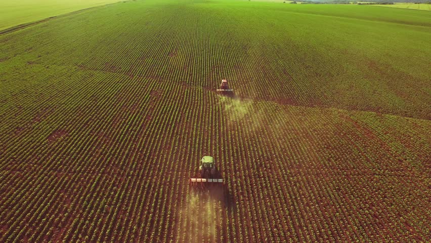 Agriculture Aerial Of Tractor Spraying Farm Land With Pesticides Farming Equipment Food Modification Crop Farming Concept