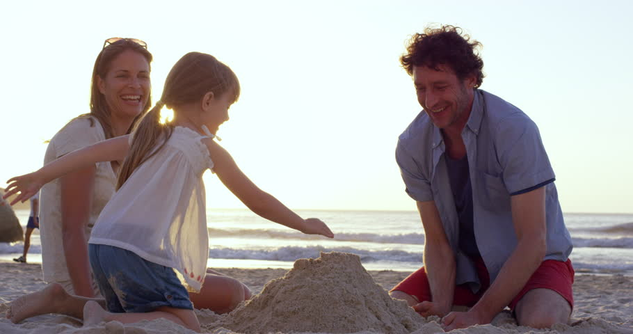 Happy family playing on the beach building sand castle at sunset on vacation slow motion RED DRAGON - 4K stock footage clip