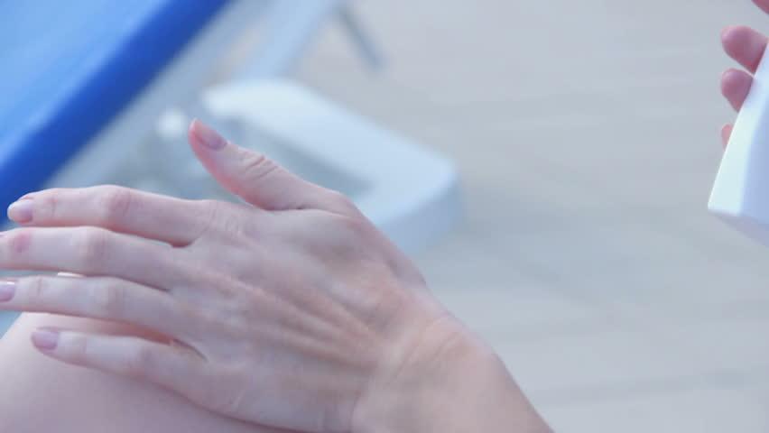 Extreme closeup, woman putting suncream on skin, rubbing legs