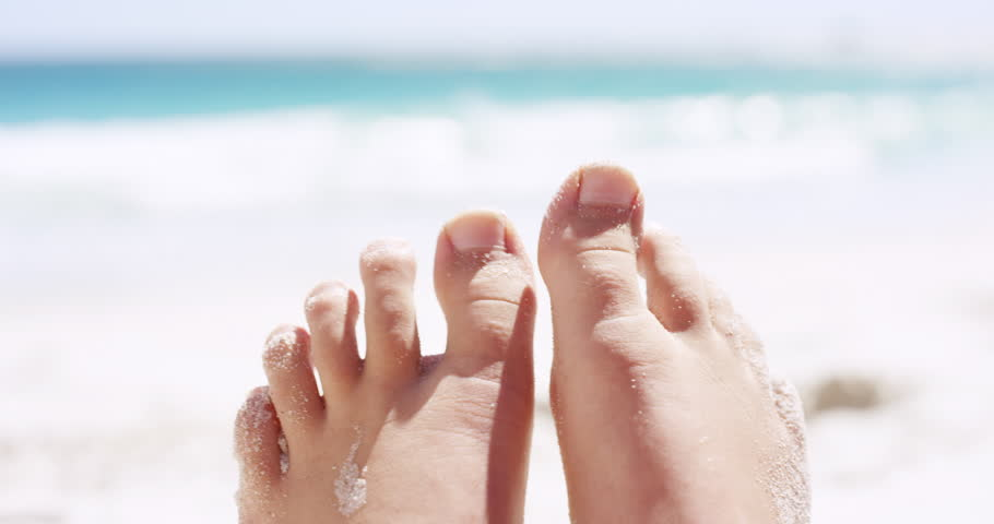 Close up of sandy feet wiggling toes on tropical beach vacation
