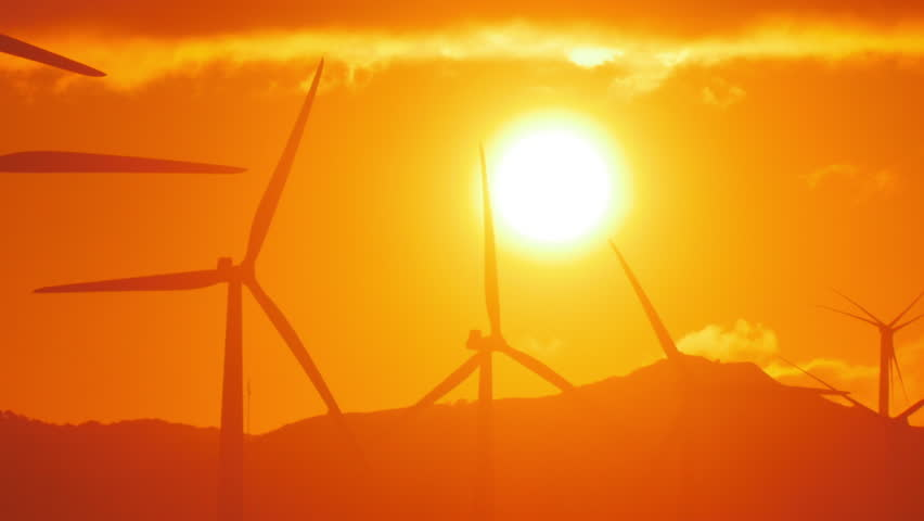 Environmental background of spinning wind mills turbines against orange sunset sky with big bright sun - HD stock video clip