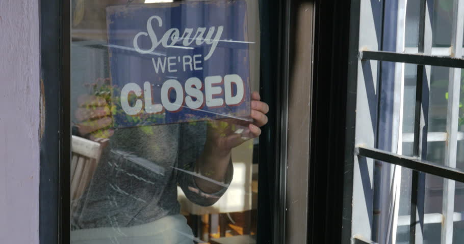 Tilt and dolly shot of a woman behind glass door of shop or cafe changing sign from closed to open