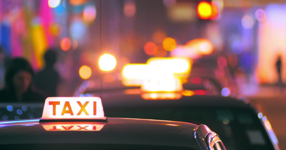 Blurred background of passenger entering inside taxi cab. Taxi sign in foreground