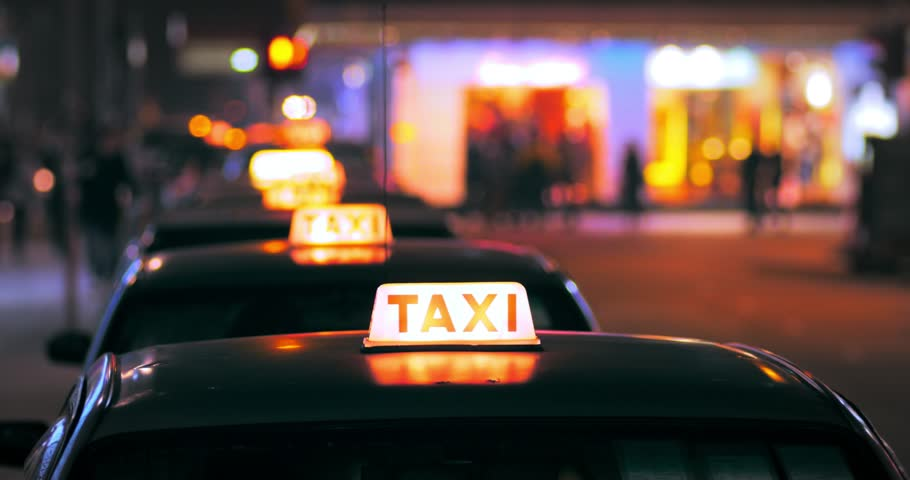 HONG KONG, CHINA - 16 JAN 2015: Unidentified driver of taxi cab looking for customers on Hongkong street at night. Blurred city lights on background