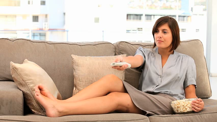 Casual brunette woman watching tv with popcorn in her living room - HD stock video clip