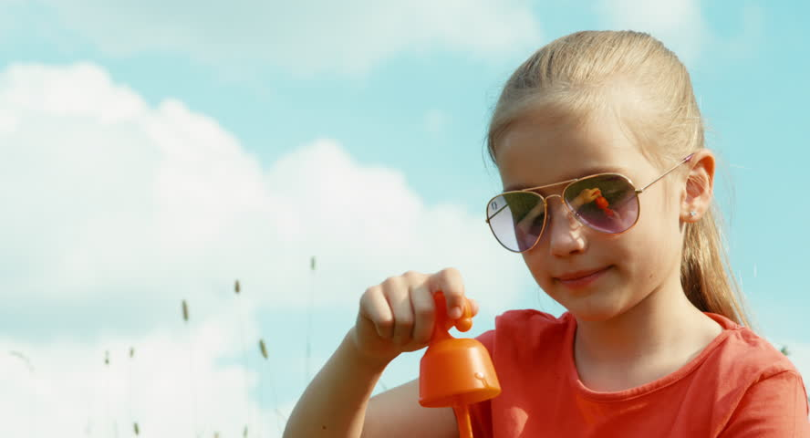 Happy girl blowing bubbles against the sky. Child sitting on the grass against the sky and smiling at camera - 4K stock footage clip