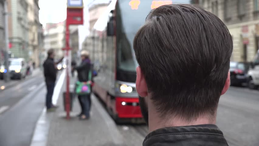 young handsome hipster man look on leaving tram from station in the city - urban street with people