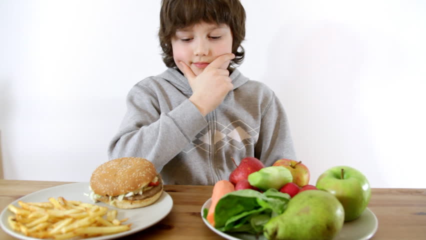 Young boy choosing vegetables and fruits instead of fast food