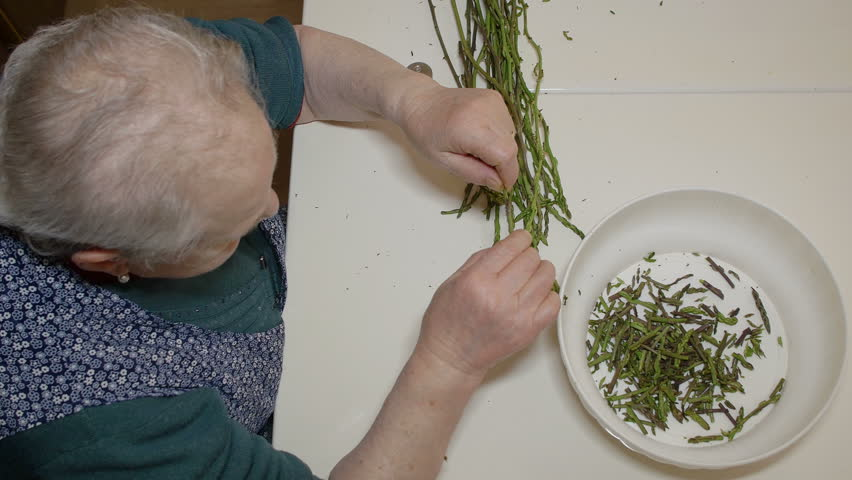 old woman preparing asparagus: peeling asparagus