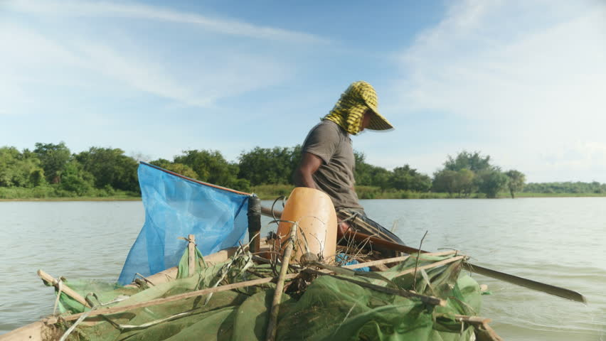 Fisherman in dugout canoe pulling drop net out of river and catching prawns ,southeast asia, cambodia