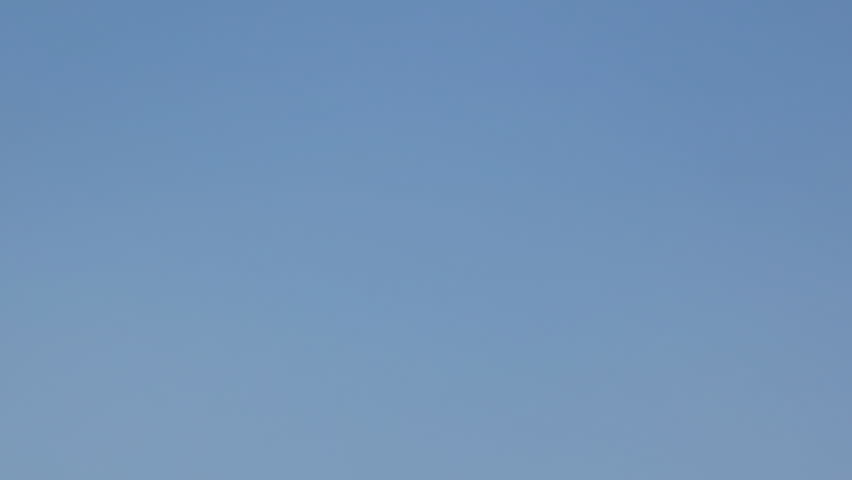 Boy clicks clapperboard and walks away against blue sky