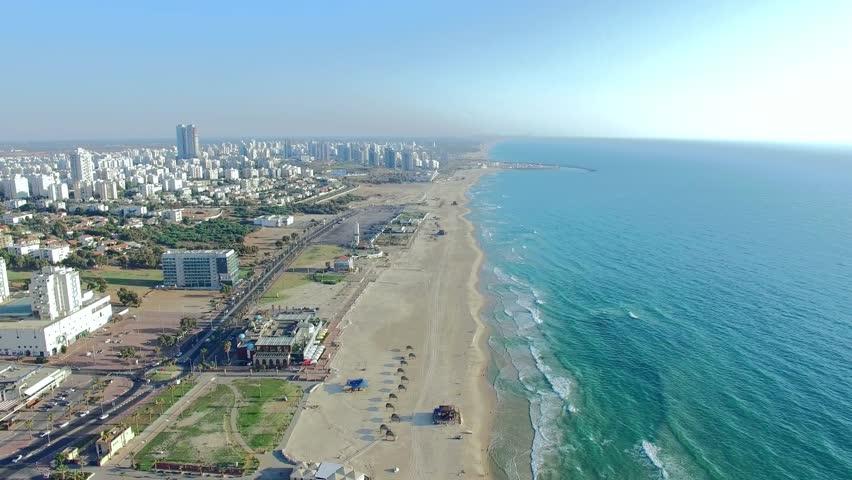 Aerial: Over City near ocean. Coastline.