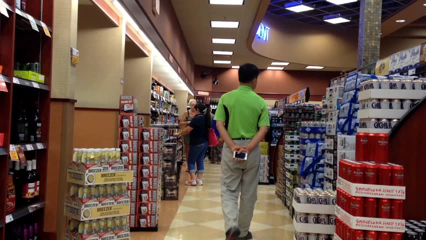 Coquitlam, BC, Canada - July 18, 2015 : Shoppers choosing beer inside BC liquor store