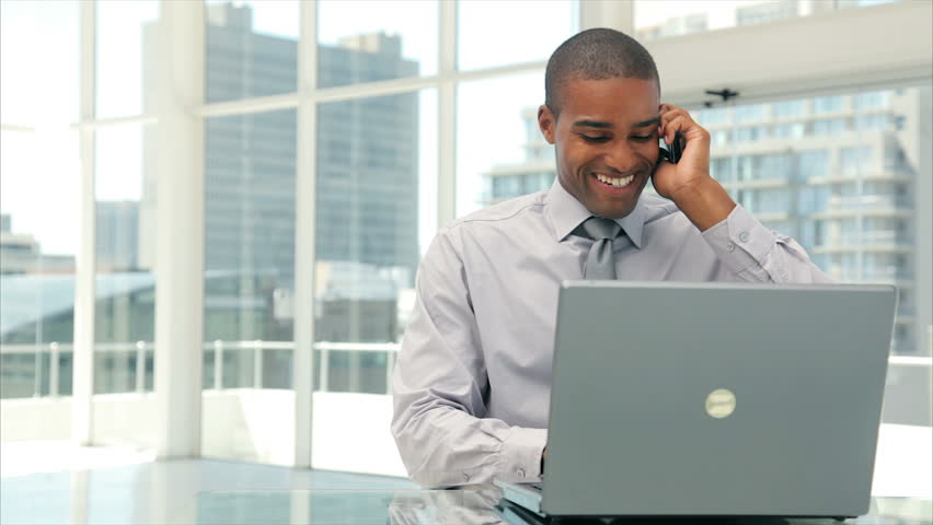 Panning shot of businessman answering smart phone while using laptop. Male executive is in formals. Smart well-dressed professional is sitting at desk in brightly lit office.