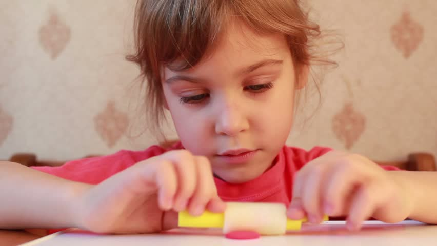 beautiful girl rolls cylinder of plasticine on table - HD stock footage clip