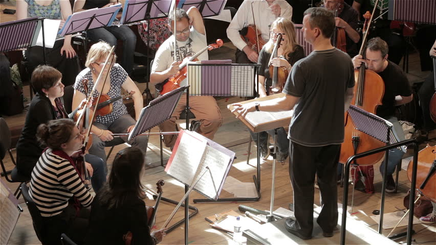 LONDON, UK - 8 JUNE 2013: Candid video footage of a conductor addressing the orchestra during a break in a classical symphony rehearsal.