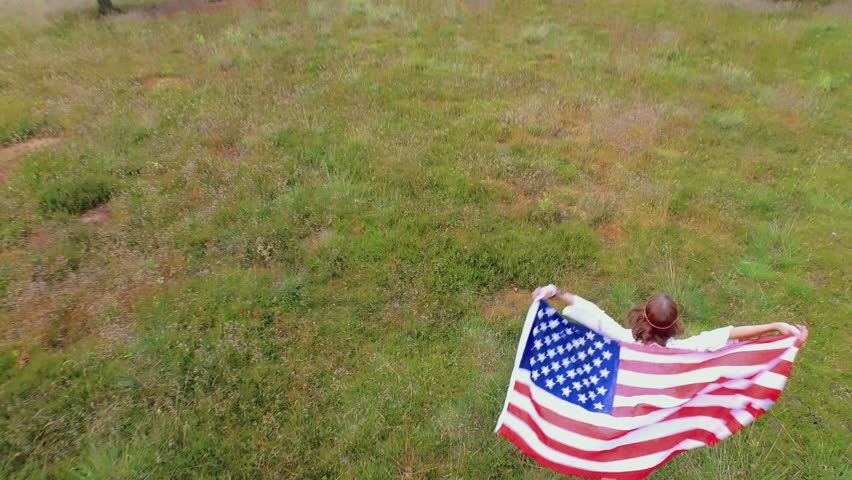 Aerial view of girl walking in park with american flag waving
