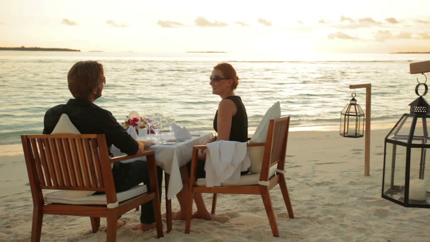 young couple sitting and dining at a tropical beach in front of the ocean at sunset with audio
