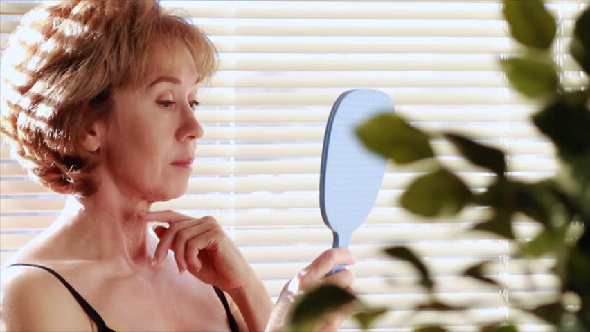 A mature woman looking in a mirror becomes unhappy with her reflection and starts to examine her aging skin. - HD stock footage clip