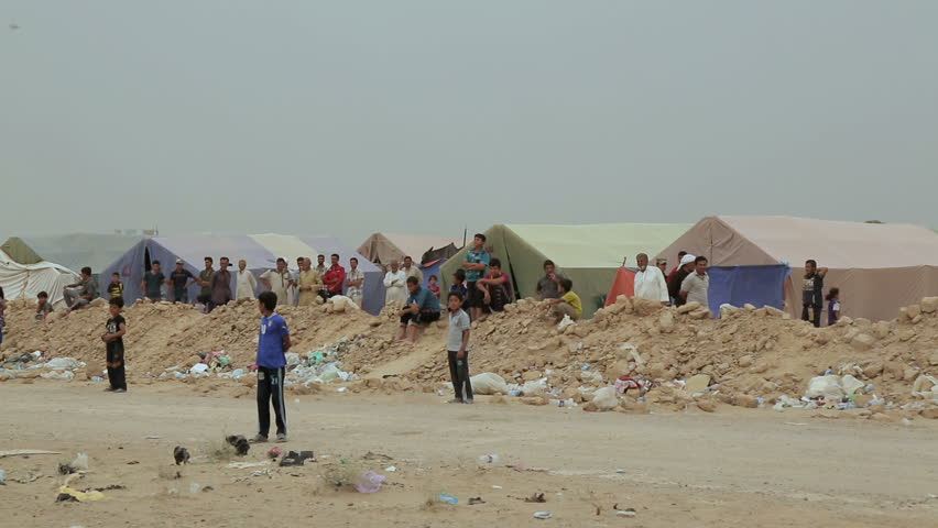 ANBAR, IRAQ - 28 MAY 2015: People stand in front of tents at a refugee camp