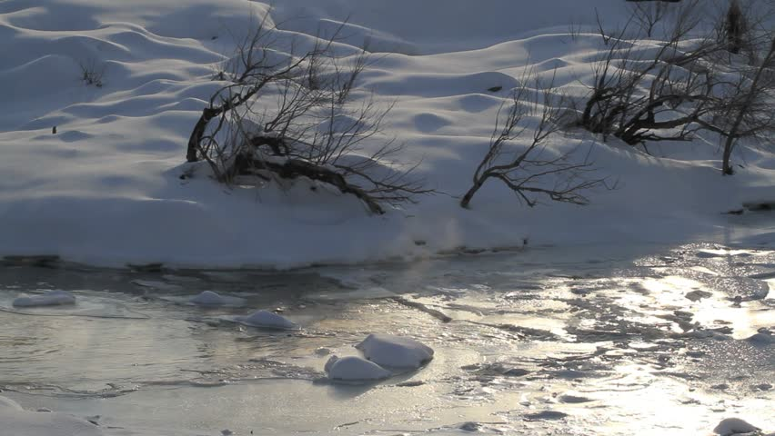 Wilderness winter leafless trees and riverbank at sunrise. Flowing water moves under snow and ice