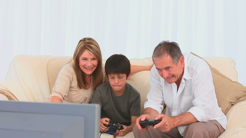 Elderly man playing video games with his grandson in the living room - HD stock footage clip