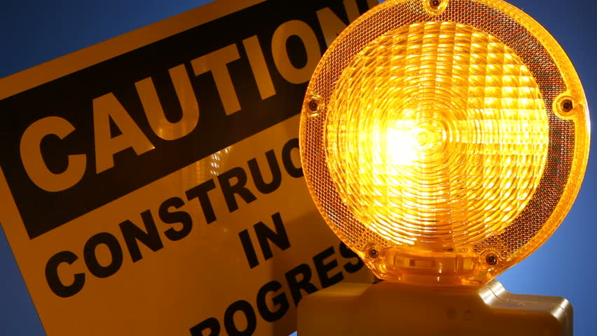 A caution sign is lit up by a blinking yellow warning light