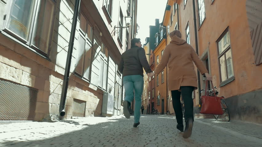 Steadicam slow motion shot of light-hearted man and woman holding hands and running along the narrow street of Stockholm, Sweden. Camera is following them.