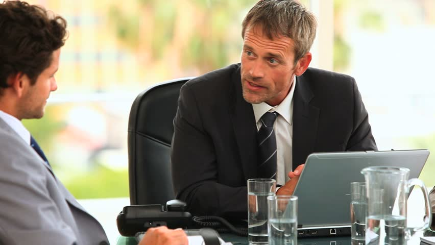 Threesome of business people during a meeting talking at an office - HD stock video clip