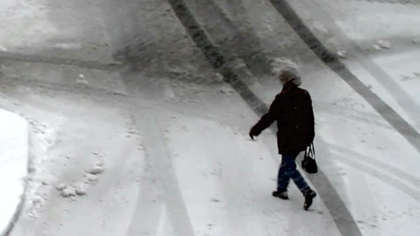 Older woman senior citizen walking through parking lot in a blizzard snow storm. View from above, late afternoon