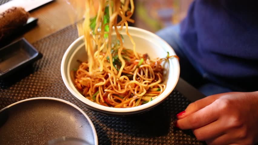 Hands of woman eating appetizing noodles in plate at table