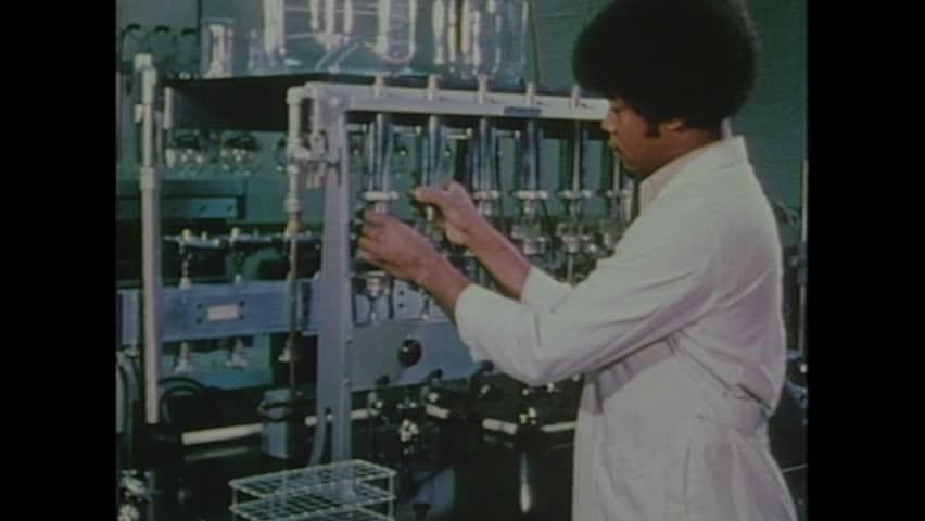 UNITED STATES 1970s: Man adjusts equipment in lab / Woman with test tubes in lab / Woman adjusts equipment in lab.