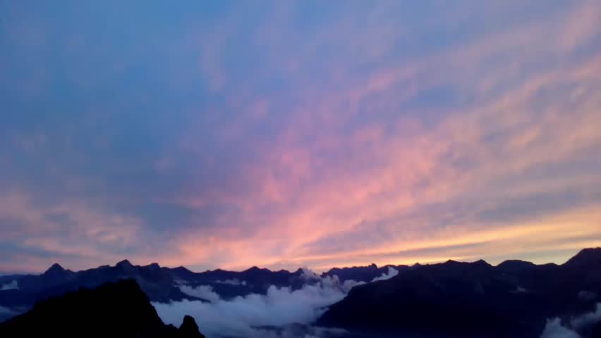 Time lapse: Sunset sky on Mountain getting darker. Mountain black profile with white clouds moving. Full HD. Italy, Alpi Cunesi.